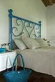 A blue wrought iron bed with white bedclothes