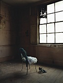 A pair of shoes and a ballet dress on a chair in an old room