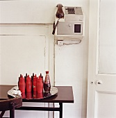 An old payphone on the wall and a tray of ketchup bottles on a table