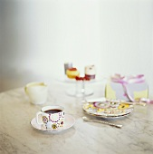 A cup of coffee, cake plate and petit fours on a table