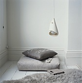 A reading corner with floor cushions, a fur rug and a pendant lamp