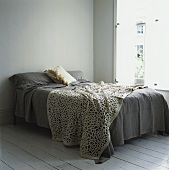 A double bed with a quilt next to a window