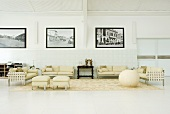 An elegant hall with cream coloured seats and black and white photos on the wall