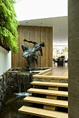 A small waterfall and a sculpture next to a flight of floating stairs in an entrance way