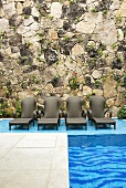 A pool with loungers against a natural stone wall