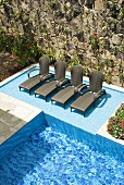 A pool with loungers in front of a natural stone wall