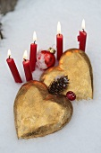 Golden hearts and red candles in the snow