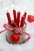 Rote Kerzen in einem Einmachglas mit Geschenkband und Weihnachtskugel im Schnee