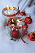 Burning candles in a jar and a Christmas baubles in the snow