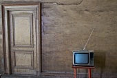 Television on a small table against a wall with a door