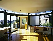 Open-plan room in contemporary penthouse with curved desk below window