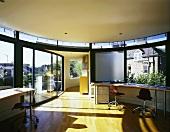 Zeitgenössisches Penthaus mit offenem Wohnraum und geschwungenem Arbeitstisch vor Fenster