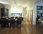 Table with upholstered chairs in an open plan kitchen-dining room with wood flooring