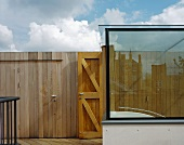 Modern glass staircase on a roof terrace and simple wooden wall with door
