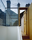 Glass staircase and open door with a view of a roof terrace