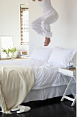 Young woman jumping on a bed