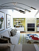 Modern sectional sofa and curved stainless steel lamp bodies in front of a fireplace and built-ins in niches