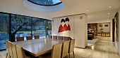 Dusk falling on a modern, newly built house with a dining table under a circular skylight in an open plan living area
