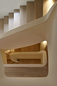 Of view through the stairwell of a modern multi-storey house with wooden steps