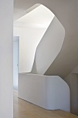 A view into a stairwell with curved steps and stone banisters