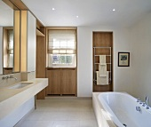 Spacious designer bath with a free standing bathtub and a narrow cubic countertop