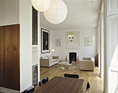 An elegant, modern open plan living room with a dining table and paper pendant lamps