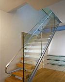 A modern stairway with a glass balustrade and a stainless steel handrail