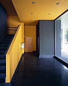 A minimalistic, arts and craft style stairway painted in strong yellow and black tones