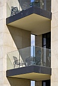 Section of a facade of a modern home, the balcony has a glass balustrade