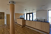 Open kitchen with wooden kitchen units in the living room with wood clad columns and wood flooring