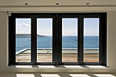 Glass patio doors in front of wood deck with a view of the ocean