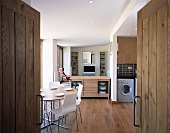 View through an open wooden double door to a dining area with white chair in front of an open kitchen-living room