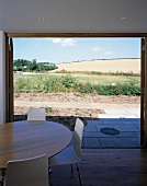 Dining table with white chairs in front of open patio doors with a view of a sunny garden