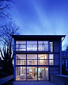 Contemporary home in the twilight with glass facade and a view of illuminated floors