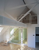 Beams stretching across a converted attic with stairs and gallery in an open living room with lighting