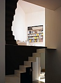 Living area with open, multi-level staircase and view of bookshelves