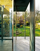 'Slice like' steel supports in front of a house with a glass facade and a view into a sunny garden