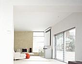 Offener Designer Wohnraum mit weißem Sofa und Sideboard neben Fenster mit halbgeschlossener Jalousie