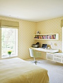 Bright bedroom with a home office in the corner and yellow patterned wallpaper on the wall