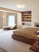 Double bed with light brown bed linen and modern divan in front of built-in shelves in a spacious bedroom