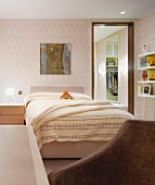 Double bed with light yellow bed linen and bright patterned wallpaper on the wall