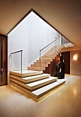 Elegant entry area with angled, stone staircase and glass banister beside a modern sculpture