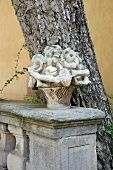 A stone flower basket in front of a tree trunk