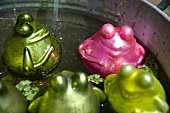 Pink and green glass frogs in a bathtub