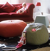 Floor cushions in front of a red sofa