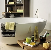 An oval shaped free standing bathtub and bath accessories