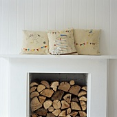 Firewood in a fireplace and decorative pillows on the mantelpiece
