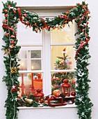 Weihnachtsfenster mit Girlande aus Grün und Lichterketten