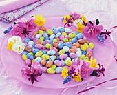 Osterteller mit Zuckereiern und Frühlingsblumen