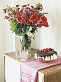 Chocolate cake with cream & raspberries beside vase of flowers